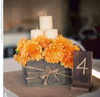 rustic box with orange flowers and candles.