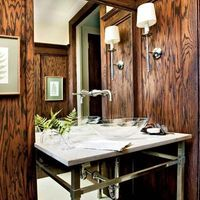 dark, wood paneling offsets a white marble countertop with a raised glass sink and steel legs in a small bathroom