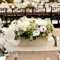 Ivory-painted wood containers were filled with low arrangements of pale-green hydrangeas, bells of Ireland and pink stock.