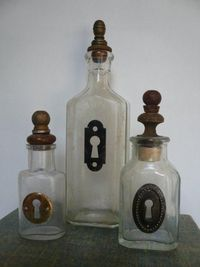 Decorate some old bottles found at the thift store~ They added Keyholes and lamp finials on these old bottles! You could also add old cheap jewelry you sometimes find at garage sales.