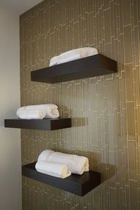 greenish-brown tile (looks like bamboo) and dark brown shelves with bright white towels