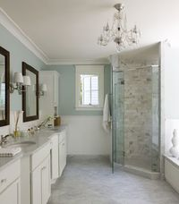 Liz Levin Interiors master bathroom with spa blue walls , chair rail with subway tiles backsplash, corner frameless glass shower, calcutta marble tiles shower surround, white carrara marble tiles floor, white double bathroom cabinets vanity with marble co...