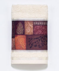 The Adirondack Pine hand towel features a decorative fabric strip filled with patterns of rustic trees and pinecones against a light neutral ivory 100% cotton towel.